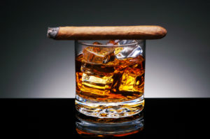 A lit cigar resting on top of a glass of whiskey and ice cubes over a spot light to dark background.